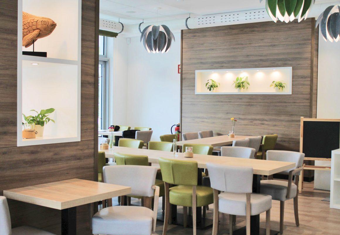 Rotheo - Gastraum mit grünen und grauen Möbeln